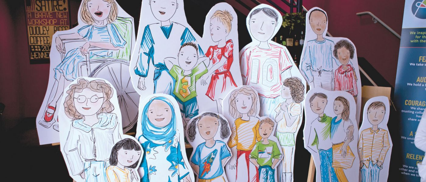 A group of life-sized cardboard cutouts of illustrated diverse children.