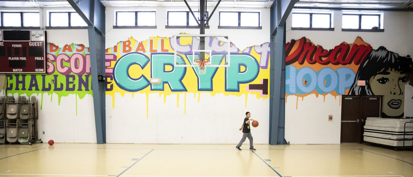 Boy bouncing basketball in a gym with colorful, expressive graffiti on walls