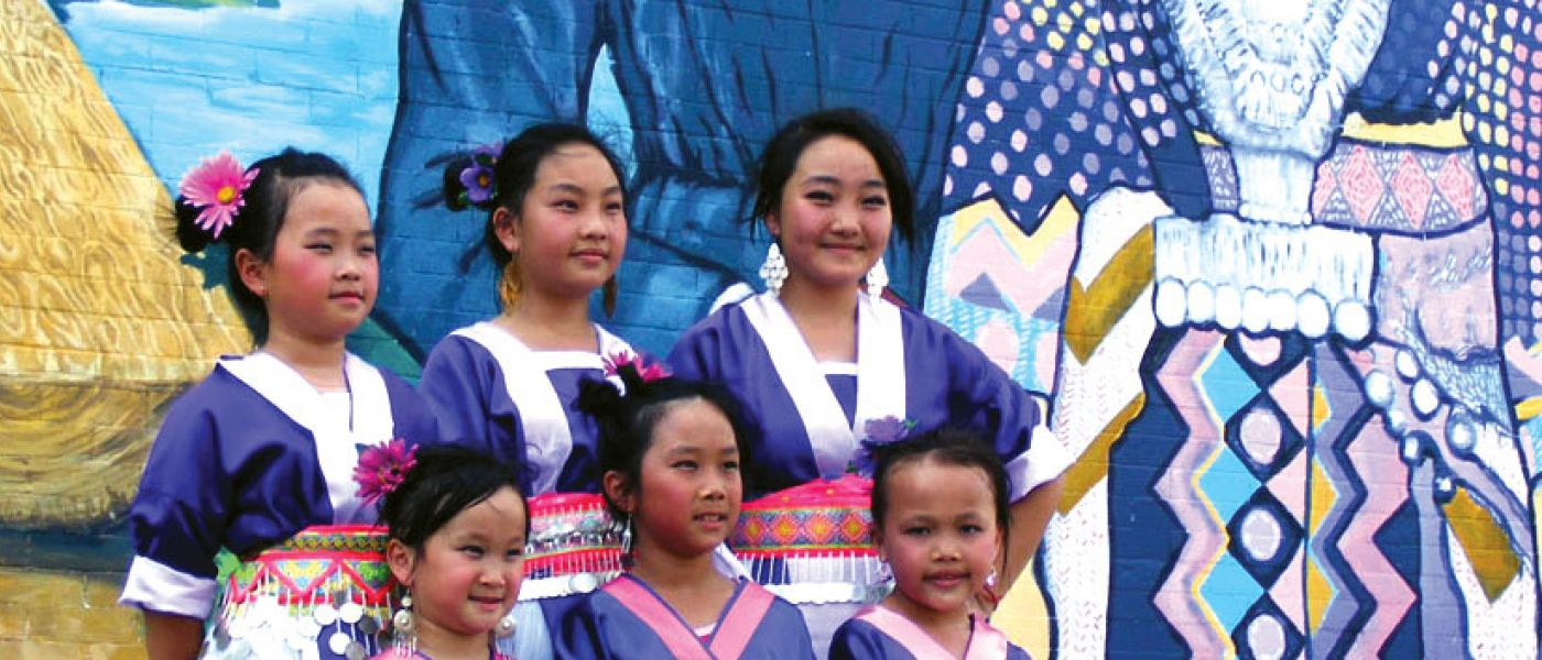 Young Hmong women in front of mural