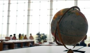 Globe and students at a table