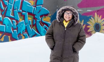 Julie Garreau in the snow and winter coat in front of graffiti art on wall