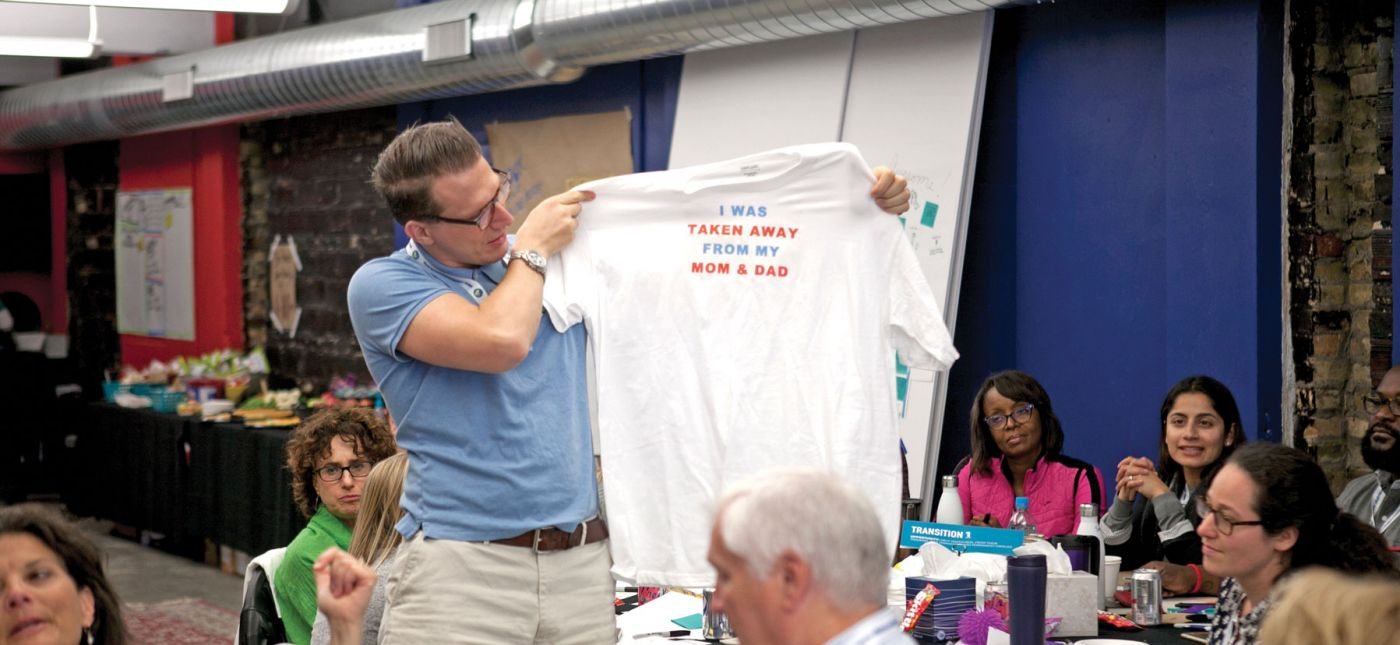"Man holding a t-shirt at the Ten for Ten conference that reads ""I was taken away from my mom and dad"""