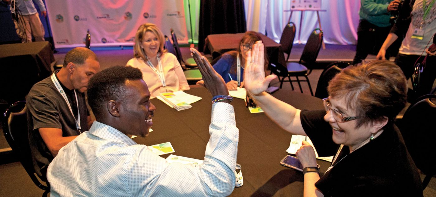 Two participants high-five at the Ten for Ten conference