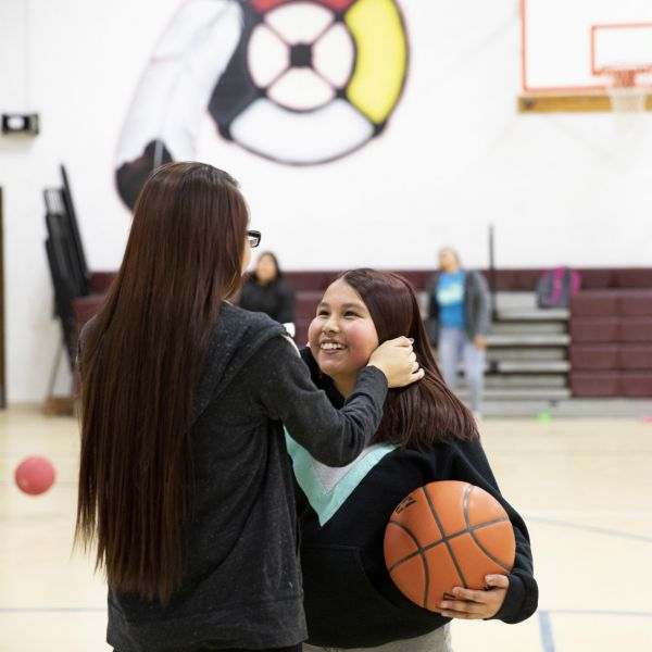 Two young women embrace on the basketball court