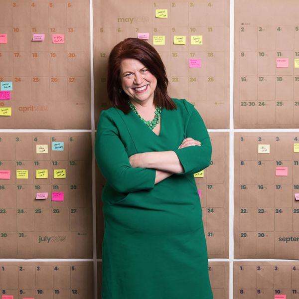 Amelia Franck Meyer standing in front of wall of colorful post-it notes