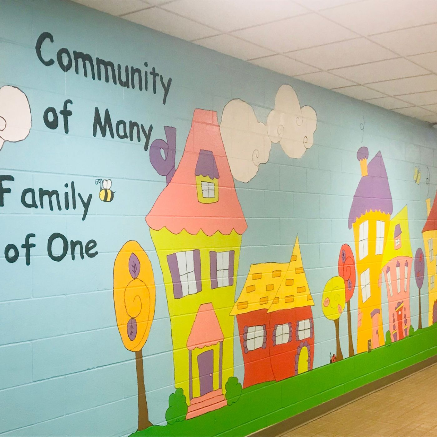 "Painted mural for colorful homes that reads ""Community of many, family of one"""